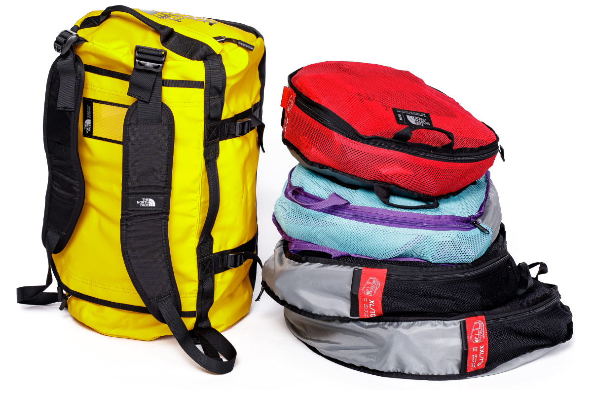 Баул The North Face Base Camp Duffle размера S. Справа — упакованные в чехлы баулы The North Face размеров M — XXL